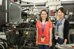 Princeton University graduate student Juliane Preimesberger (left) and postdoctoral researcher Sally Kang stand next to their experiment studying piezoelectrochemical effects in lithium-ion batteries using the VULCAN instrument at ORNL's Spallation Neutron Source. (Credit: ORNL/Genevieve Martin)
