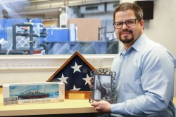 ORNL researcher Matt Stone keeps a scale model of the USS Indianapolis in his office as a tribute to his grandfather, who served aboard the ship during its top-secret mission to deliver weapons that would be used to end World War II. In its infancy, neutron scattering played a role in developing those weapons as part of Manhattan Project. Today, Stone uses neutrons to study materials that are used to improve life around the world. (credit: ORNL/Genevieve Martin)