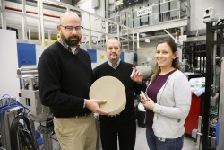 ORNL researchers Todd Toops, Charles Finney, and Melanie DeBusk (left to right) hold an example of a particulate filter used to collect harmful emissions in vehicles. Using neutrons, they are cultivating a better understanding of how heat treatments and oxidation methods can remove layers of soot and ash from these filters, which could lead to improved fuel efficiency. (Image credit: ORNL/Genevieve Martin)