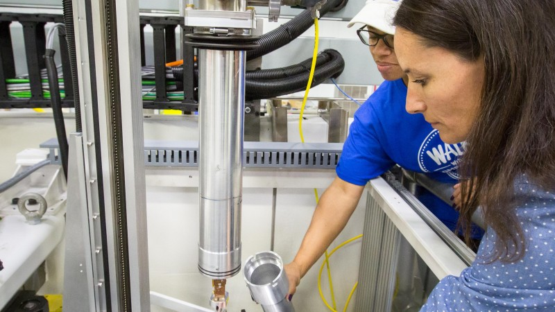 Instrument scientist Flora Meilleur (right) and scientific associate Lakeisha Walker (left) prepare to load a sample onto the CCR cold finger. Temperature is controlled by a LakeShore model 340 cryogenic temperature controller (not shown; LakeShore Cryotronics, Inc.). The inner heat shield (not shown) and outer vacuum can are made of amorphous aluminum to minimize background. Image credit: Genevieve Martin/ORNL