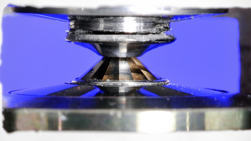 Researchers at the Spallation Neutron Source are studying materials under extreme pressure using diamond anvil cells. Diamond anvil cells are created using diamonds that have been polished to create flat surfaces. The researchers  then press a sample between those surfaces with immense force to create an extreme experimental environment. This large volume neutron diamond anvil cell seen here is loaded with water (i.e. ice). The sample sits between the two diamonds. Image credit: Jason Richards/ORNL.