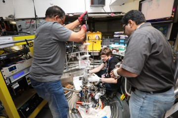Jonathan Morris, center, works with ORNL scientists Saad Elorfi and Arnab Banerjee to retrieve his ice crystal from a cryogenic chamber at the Spallation Neutron Source's ARCS instrument. (Credit: ORNL/Genevieve Martin)